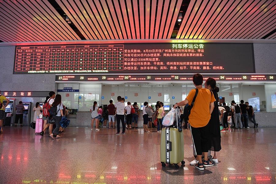 經南廣、貴廣鐵路進入廣東的157趟動車組列車23日臨時停運。圖為8月23日,廣西南寧東站售票大廳內,一名旅客從退票改簽窗口經過。(大紀元資料室)
