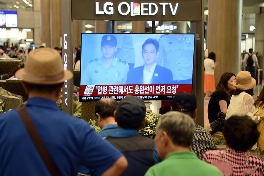 以涉嫌向前總統朴槿惠行賄等罪名被起訴的三星副會長李在鎔,8月25日在一審中被判5年徒刑。圖為25日下午仁川機場的旅客在觀看相關的新聞。(newsis)