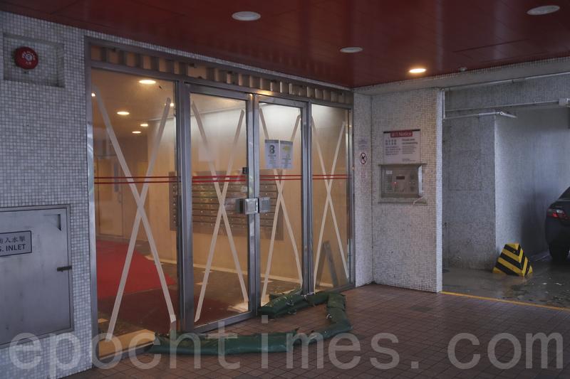 杏花邨管理處派人在大廈大堂玻璃門貼上封箱膠紙,又在地上堆疊起沙包。(余鋼/大紀元)