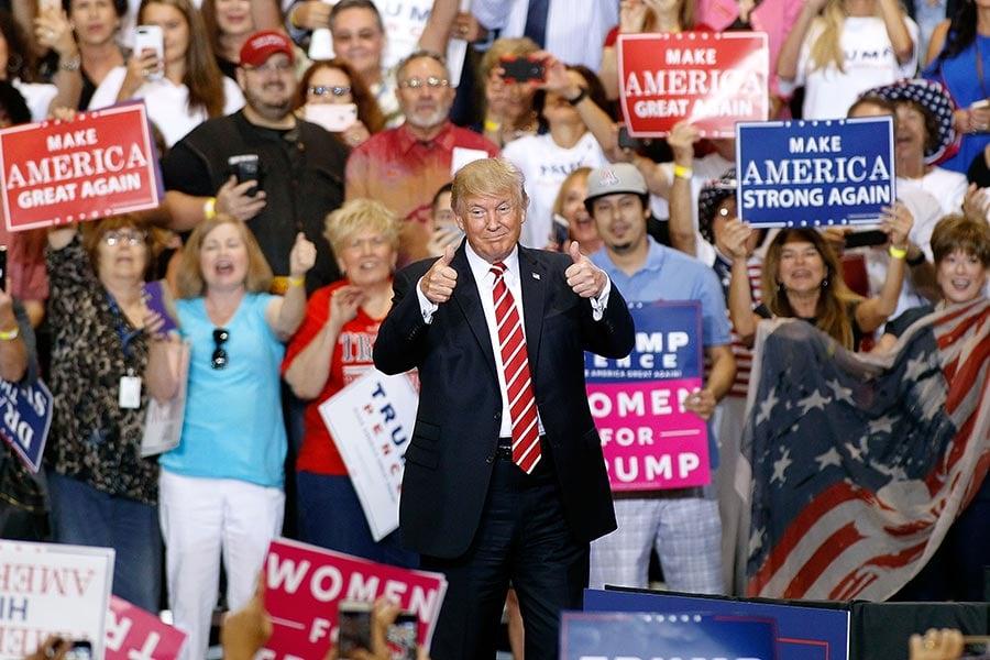 圖為8月22日,特朗普在美國亞利桑那州鳳凰城的一場集會中發表演說,並與支持者互動。(Ralph Freso/Getty Images)
