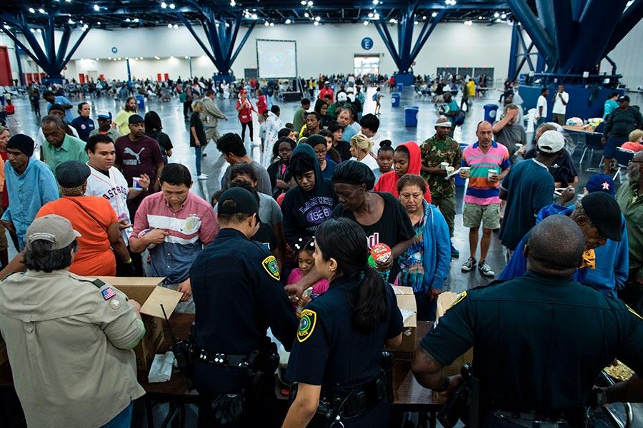 哈維颶風對德克薩斯州侯斯頓造成嚴重洪災。圖為8月28日,災民在喬治・佈朗會議中心的收容所領取食物。(BRENDAN SMIALOWSKI/AFP/Getty Images)
