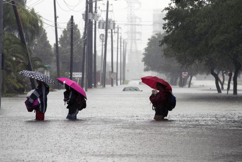 哈維颶風襲擊德州,侯斯頓遭遇前所未有的洪災。圖為2017年8月28日,德州侯斯頓,水患嚴重,民眾涉水撤離災區。(Erich Schlegel/Getty Images)