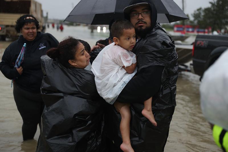2017年8月28日,德州侯斯頓,哈維颶風侵襲德州引發嚴重洪災,受困民眾互助撤離災區。(Joe Raedle/Getty Images)
