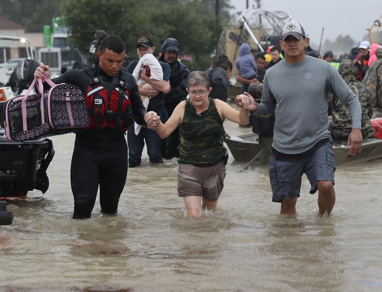 2017年8月28日,德州侯斯頓,哈維颶風侵襲德州引發嚴重洪災,救難人員和當地民眾協助救援。(Joe Raedle/Getty Images)