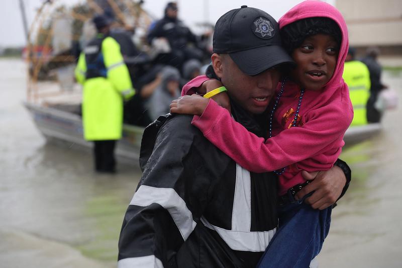 2017年8月28日,德州侯斯頓,哈維颶風侵襲德州引發嚴重洪災,救難人員抱著民眾離開洪災地區。(Joe Raedle/Getty Images)