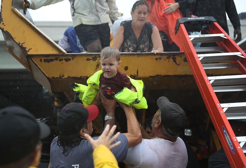 哈維颶風在德州侯斯頓造成嚴重洪災後,普通市民加緊互助。2017年8月28日,德州侯斯頓,民眾協助受困民眾。(Joe Raedle/Getty Images)