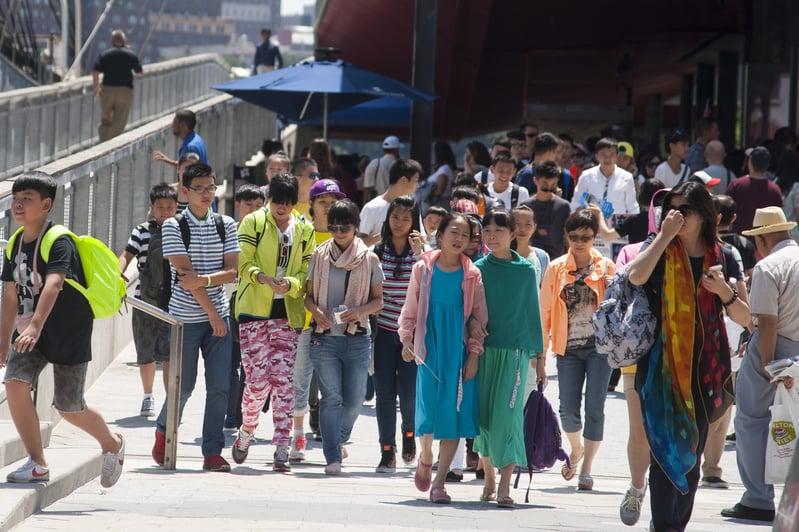 最近乘坐中國國航來往於美國的乘客大幅減少,導致該公司考慮是否要減少一些班次。圖為抵達美國華盛頓DC旅遊的中國遊客。(TIM SLOAN/AFP)
