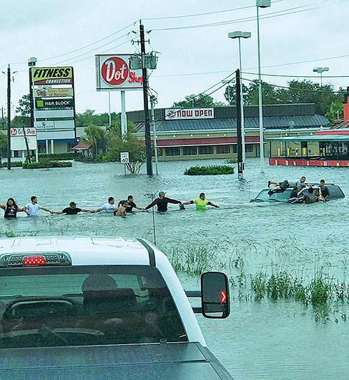 十多名民眾築城人鏈,營救被洪水圍困在車中的一位老人。(ABC13 Houston推特)