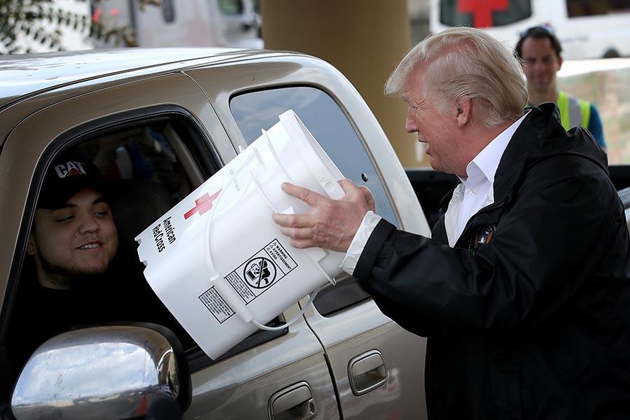 9月2日,特朗普夫婦訪問德州東南部受哈維颶風襲擊嚴重的地區。圖為特朗普準備將救災物品裝到一位受災居民的車上。(Win McNamee/Getty Images)