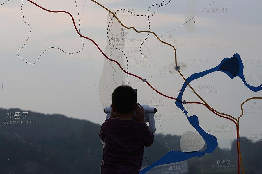 北韓3日宣佈在咸鏡北道吉州郡豐溪里進行第六次核試。圖為北韓核試驗後,一名南韓男孩用雙筒望遠鏡觀察北韓。(Chung Sung-Jun/Getty Images)