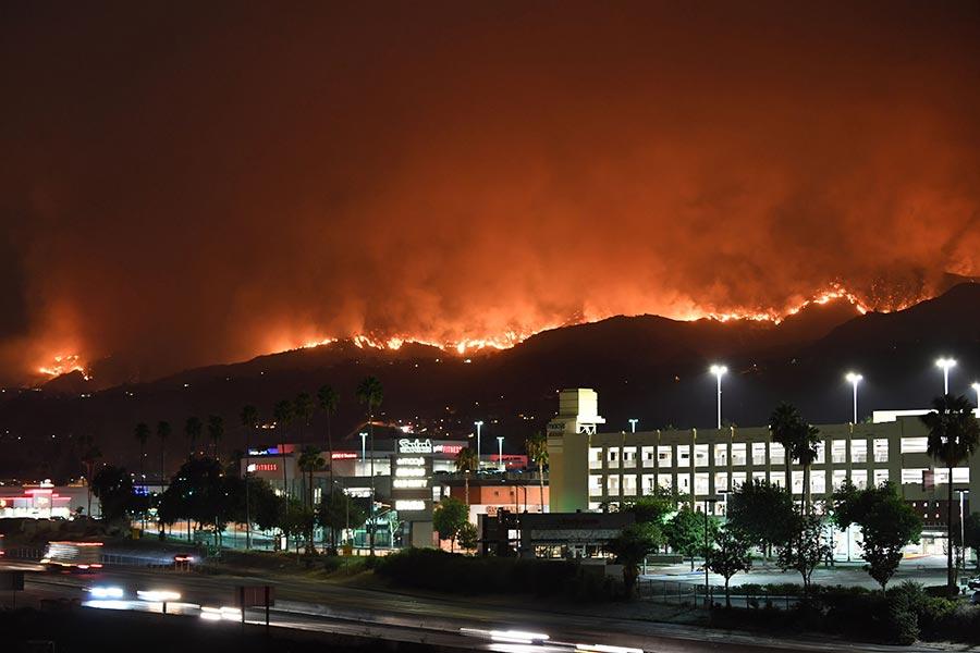 2017年9月2日,加州洛杉磯的消防隊員在山上架設水管滅火。山火造成8000公頃土地過火,並摧毀了三座建築物居民被強制撤離。這是洛杉磯市史上面積最大的山火。(ROBYN BECK/AFP/Getty Images)