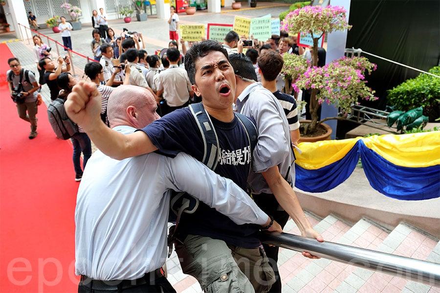 十多名關注組成員開學禮入口處高呼口號抗議,期間一度試圖衝入會場,但被保安阻止。(李逸/大紀元)