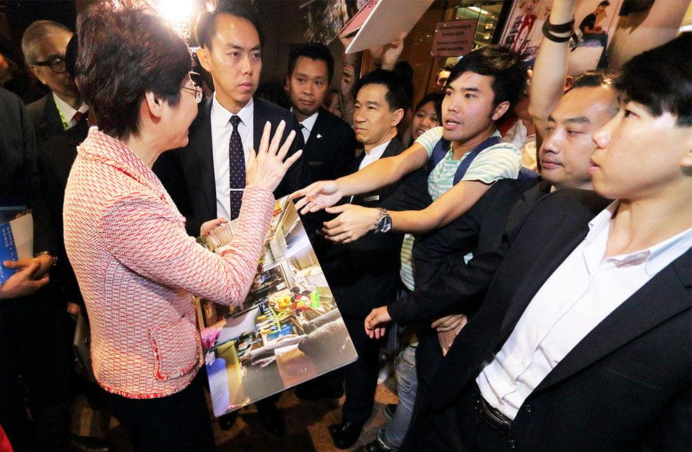 林鄭月娥昨晨出席房屋論壇期間,關注基層住屋聯席到場抗議,向她遞上劏房照片(相關報道見A2)。(蔡雯文/大紀元)