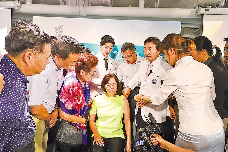 申俊湜邀請現場中醫師到台前觀看診治示範。(余鋼/大紀元)