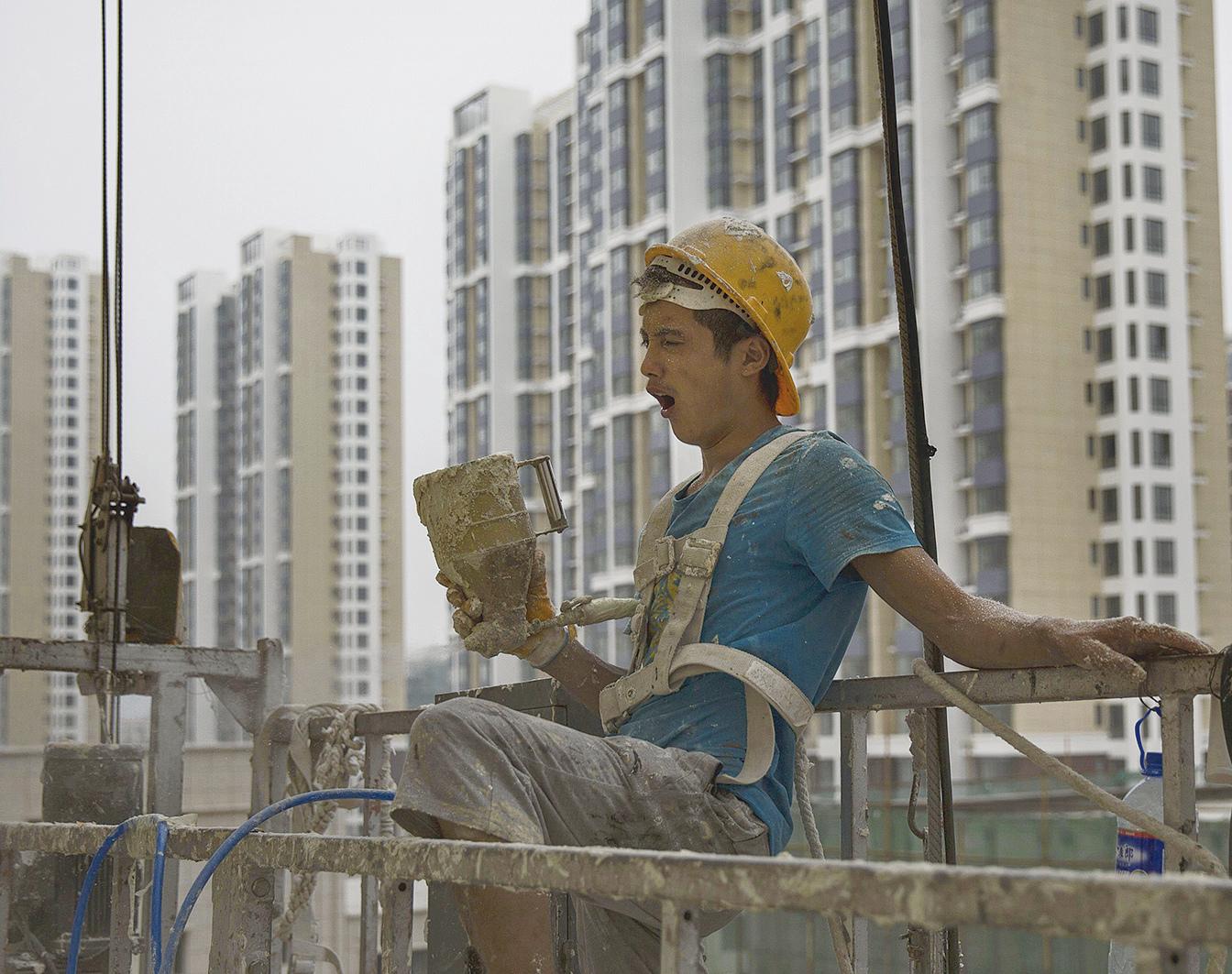 最近一年內,北京樓市進行了近50次調控,目前,房價比去年底平均每平米下降1萬元左右。圖為北京施工地盤上一名在休息的建築工人。(Getty Images)