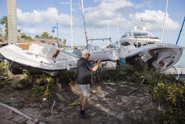 一名男子於9月11日在佛羅里達州邁阿密的一個碼頭拍攝遭颶風艾爾瑪損壞的船隻。(AFP PHOTO / SAUL LOEB)
