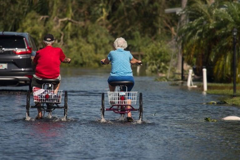 兩名老年人在佛羅里達州那不勒斯淹水街道上騎三輪車。(AFP PHOTO / NICHOLAS KAMM)