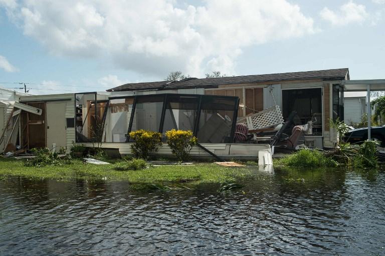 佛羅里達州那不勒斯街道上遭洪水損毀的房屋。(AFP PHOTO / NICHOLAS KAMM)