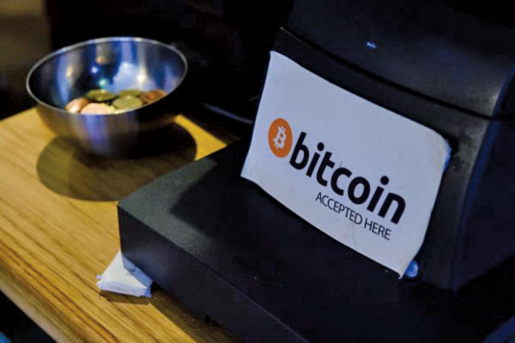 圖為一家咖啡店內立著牌子,表示接受比特幣支付。(Getty Images)