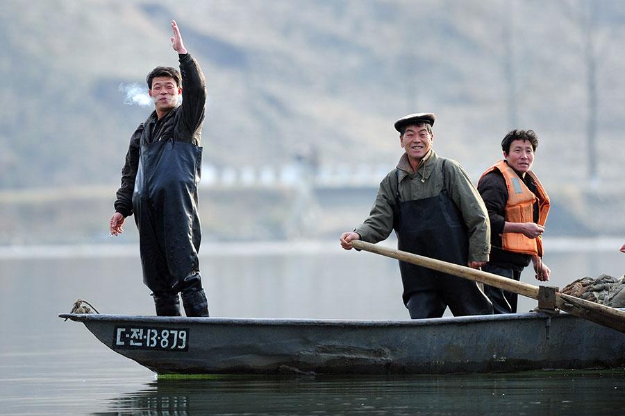 北韓漁夫向中國遊客打招呼。(FREDERIC J. BROWN/AFP/Getty Images)