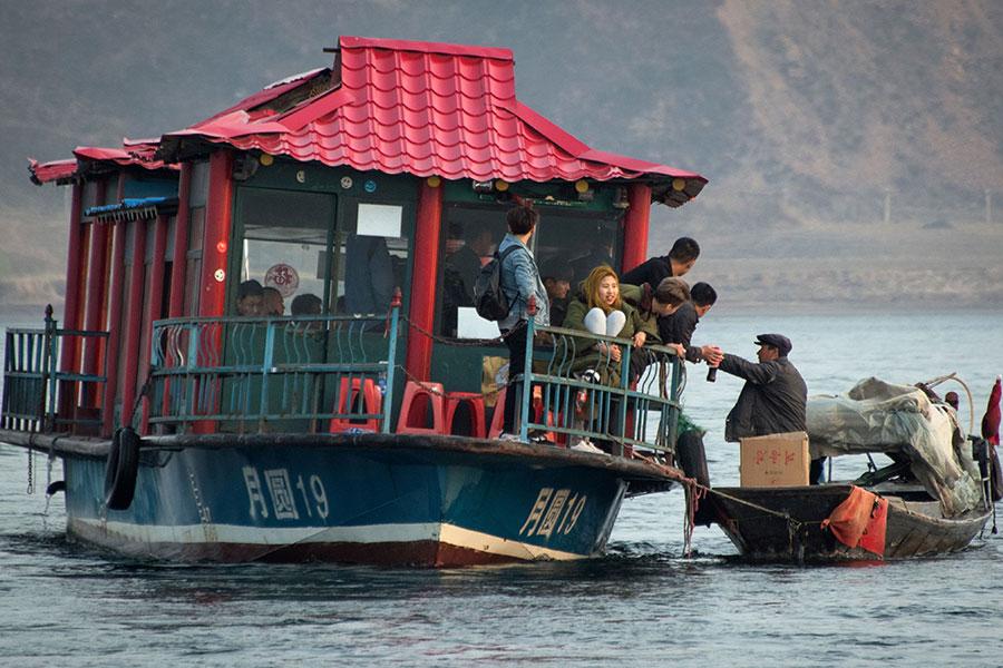 北韓男子(右)在鴨綠江沿岸向中國遊客出售北韓產品。(JOHANNES EISELE/AFP/Getty Images)