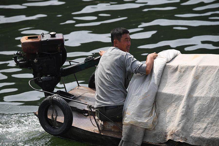 一艘北韓漁船靠上中國遊船兜售商品。(GREG BAKER/AFP/Getty Images)