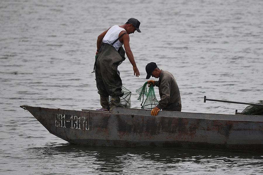 兩名北韓男子在鴨綠江上打魚。(GREG BAKER/AFP/Getty Images)