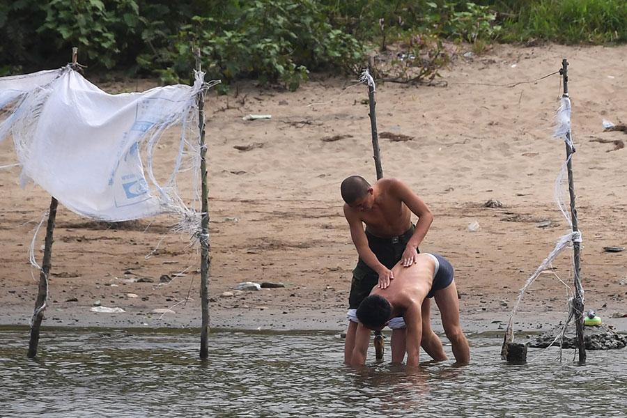 北韓邊境小鎮新義州的兩名北韓人在洗浴。(GREG BAKER/AFP/Getty Images)