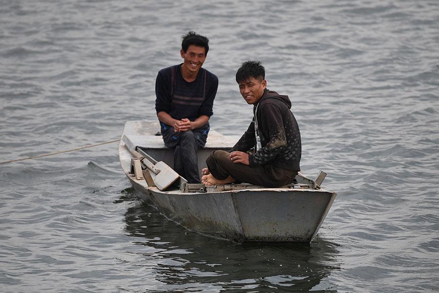 兩名北韓男子在鴨綠江上向中國遊客微笑。(GREG BAKER/AFP/Getty Images)
