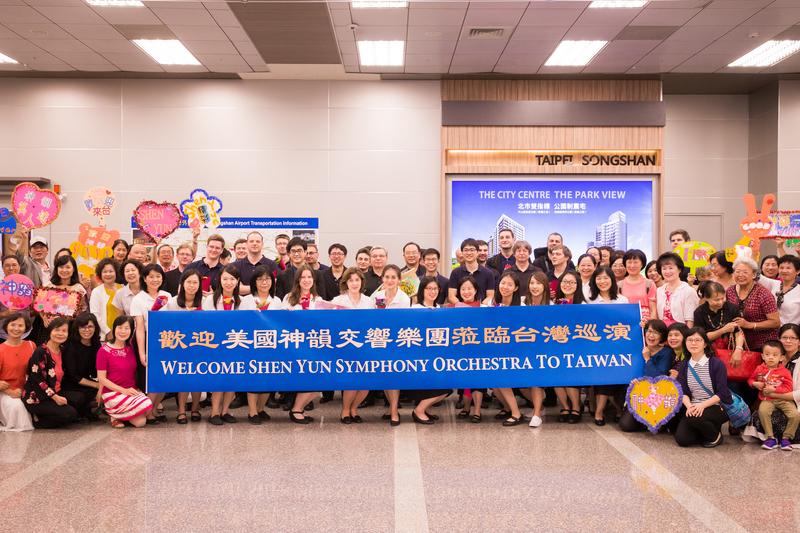 美國神韻交響樂團9月19日晚間抵達松山機場,熱情粉絲獻花跟偶像們合影。(陳柏州/大紀元)