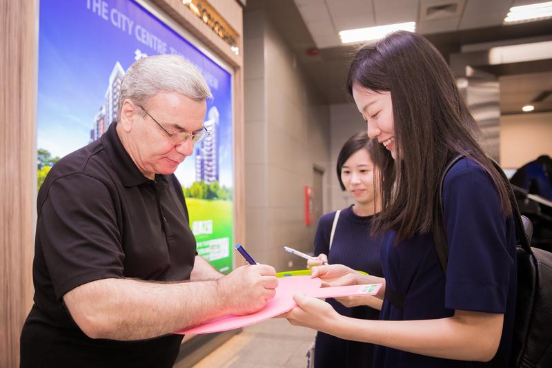 美國神韻交響樂團9月19日晚間抵達松山機場,樂團指揮米蘭・納切夫(Milen Nachev)為粉絲簽名。(陳柏州/大紀元)