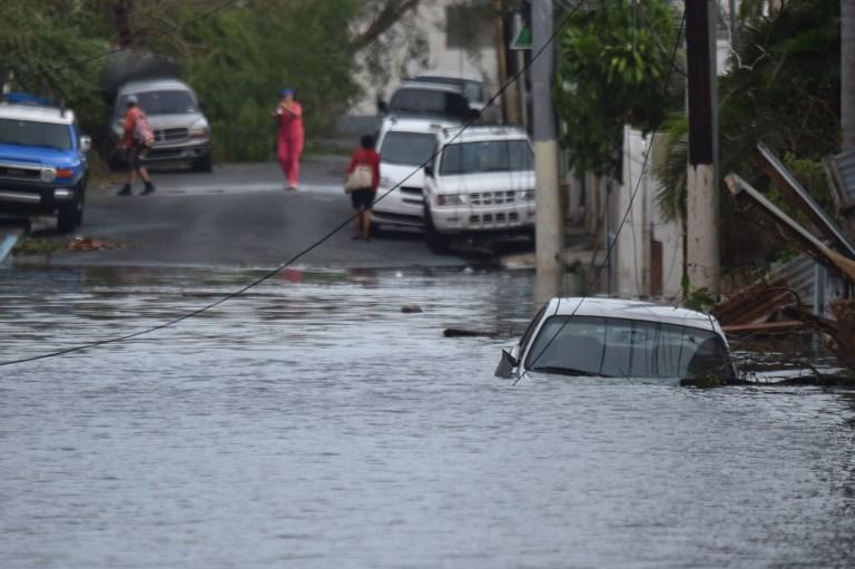 9月21日,一輛汽車被困在波多黎各聖胡安的淹水街道。(AFP PHOTO / HECTOR RETAMAL)