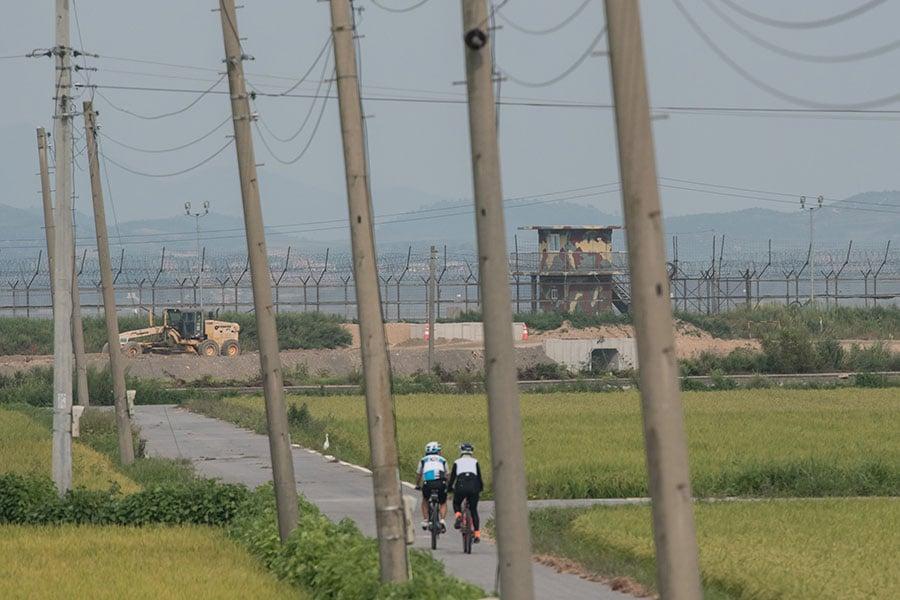 自行車騎士經過非軍事區的南韓守衛。(ED JONES/AFP/Getty Images)