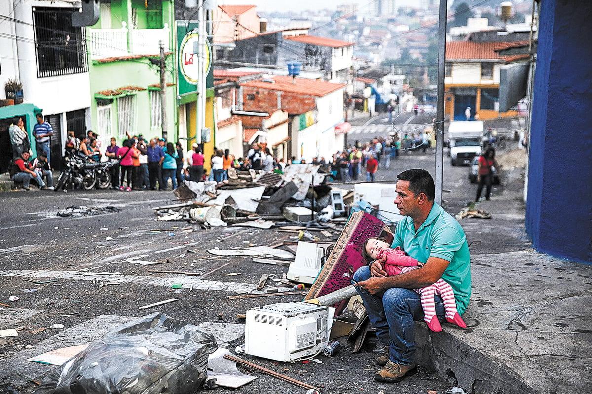 世界上沒有哪個國家像委內瑞拉曾經這樣富有、而潰敗起來又是如此迅猛。背後原因,引人深思。圖為一位父親和女兒坐在委內瑞拉一個城市破敗的街頭,而背景是購買必需品的長隊。(Getty Images)