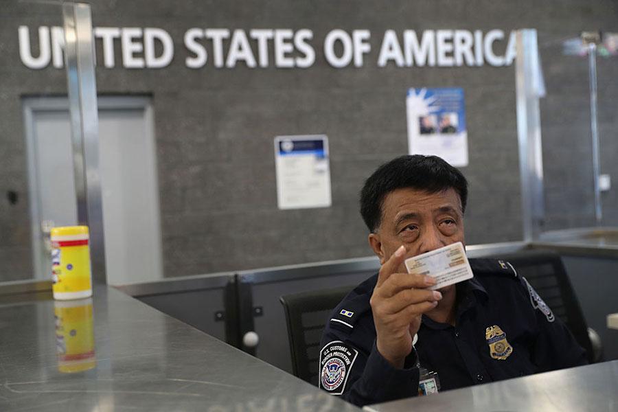 美國總統特朗普的90天旅行禁令,於9月24日到期。預計特朗普政府很快將宣佈有關外國人入境美國的新規生效。圖為美國一海關人員在檢查入境遊客的證件。(John Moore/Getty Images)