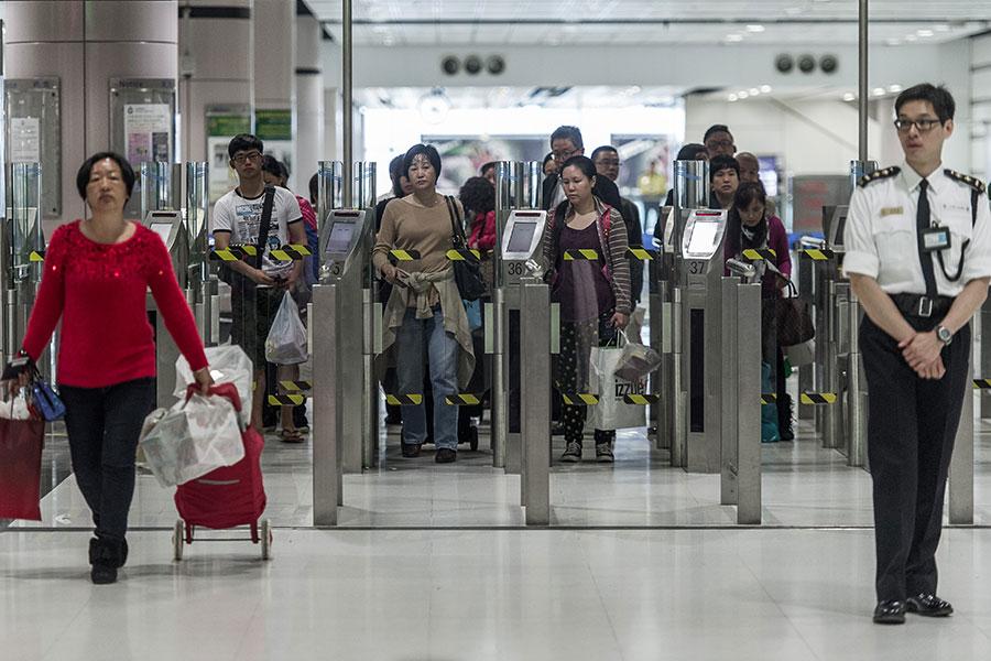 圖為使用陸路口岸過境前往內地的旅客。(PHILIPPE LOPEZ/AFP/Getty Images)