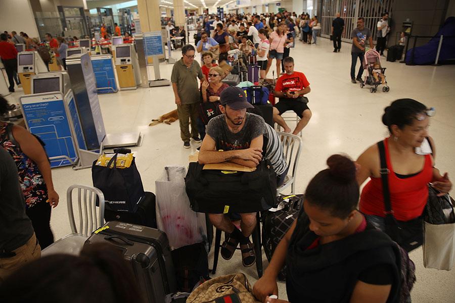旅客在聖胡安市內的機場大排長龍,等待一票難求的機位。(Joe Raedle/Getty Images)