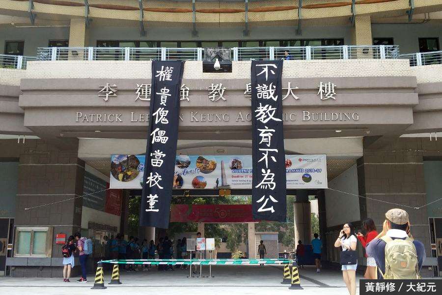 嶺大校園的主教學大樓外今日懸掛起「不識教育不為公,權貴傀儡當校董」的直幡,呼應遊行訴求。(黃靜修/大紀元)