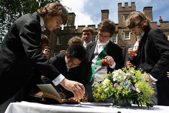 畢業班學生離開學校前,在畢業生簽名簿上籤上自己的名字。(Christopher Furlong/Getty Images)