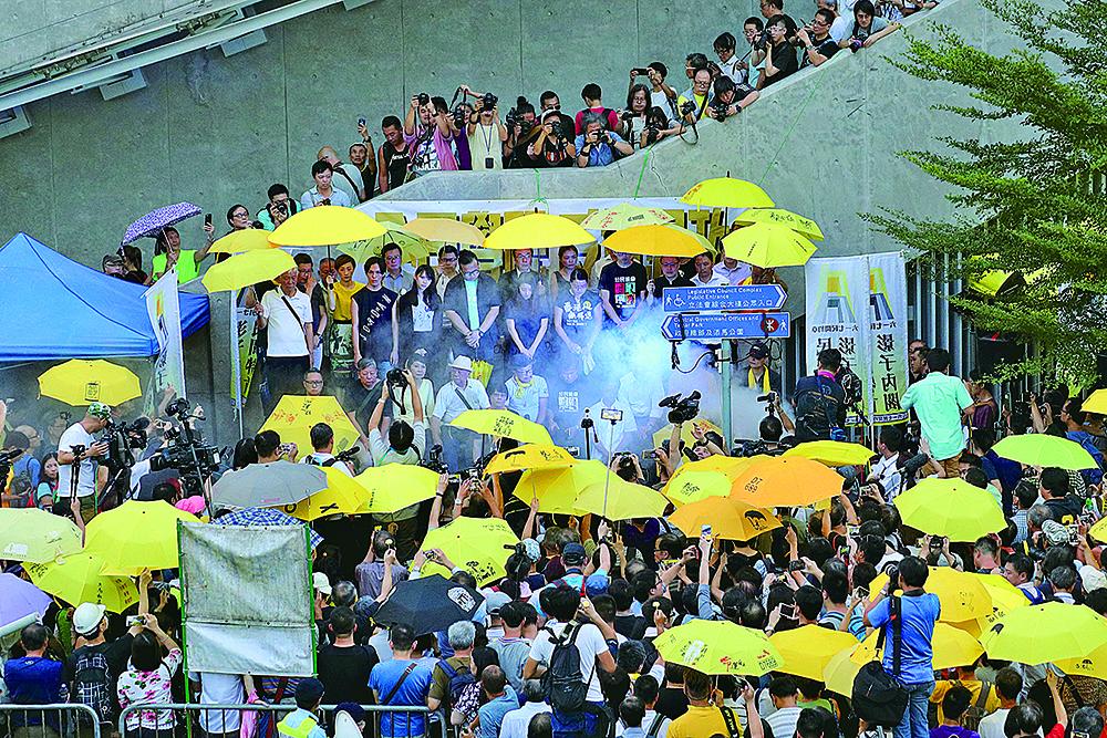 雨傘運動三周年,多個團體在金鐘「連儂牆」舉行「全民覺醒反抗暴政」集會。下午5時58分,大會以水蒸氣重現當年警察施放第一枚催淚彈情景,並默站3分鐘紀念。(李逸/大紀元)