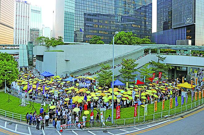不少當年參加過佔領行動的人撐起黃雨傘重回舊地,寓意延續雨傘運動精神。(李逸/大紀元)