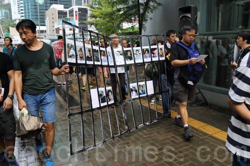 有市民手持貼上16名良心犯相片的道具。(蔡雯文/大紀元)