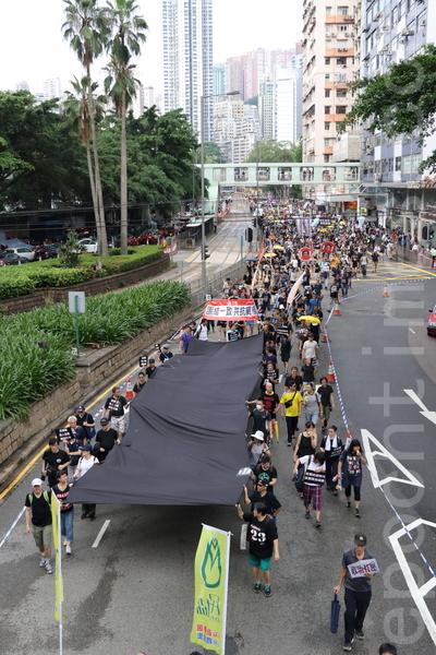 遊行由團體代表帶頭手持一塊黑布代表政府實施威權管治帶來黑暗。(蔡雯文/大紀元)
