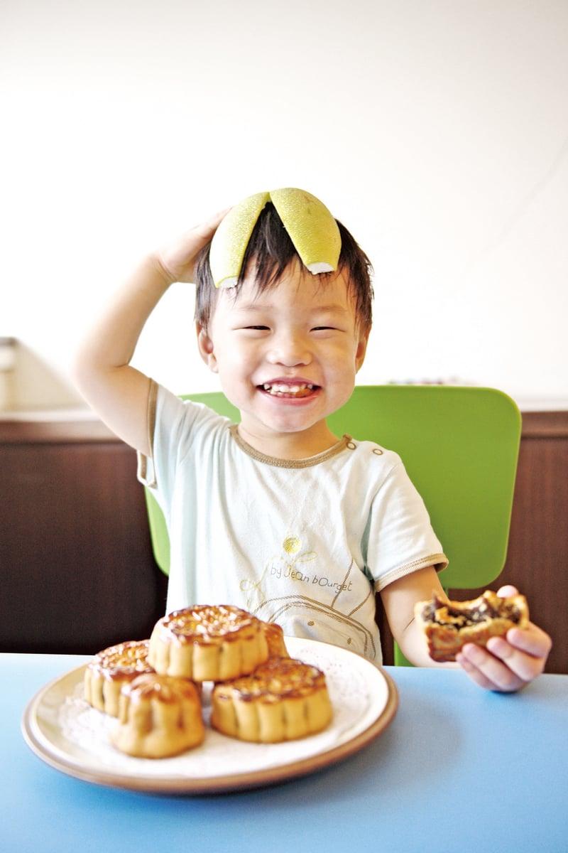 孩子開心地帶著柚子帽,吃著月餅。