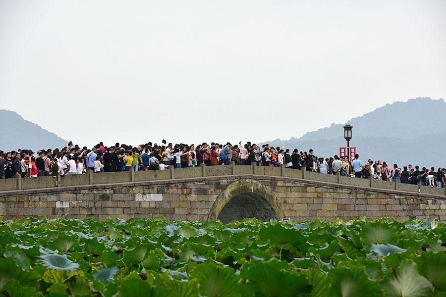 大陸十一長假首日,國內遊客被堵在高速。之後,北京、杭州、蘇州、南京等地景區遊客爆滿。有遊客稱,杭州西湖的斷橋真要「斷」了。(Xu Hui/VCG/Getty Images)
