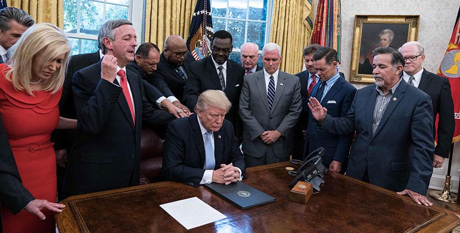 圖為9月3日,特朗普就颶風哈維吹襲美國之事,與牧師及團隊人員,在白宮內手拉手低頭向神祈禱。(NICHOLAS KAMM/AFP/Getty Images)
