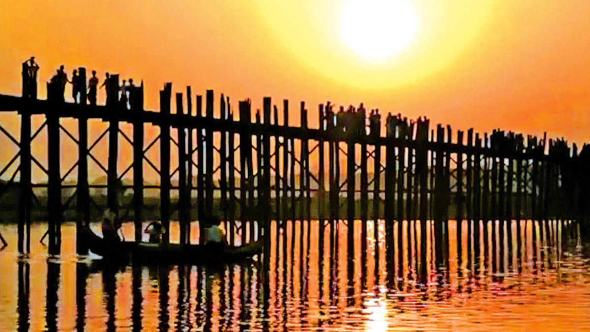 落日中的烏本橋,長長的橋墩插在水中,在夕陽中讓她的長腳顯得更長。