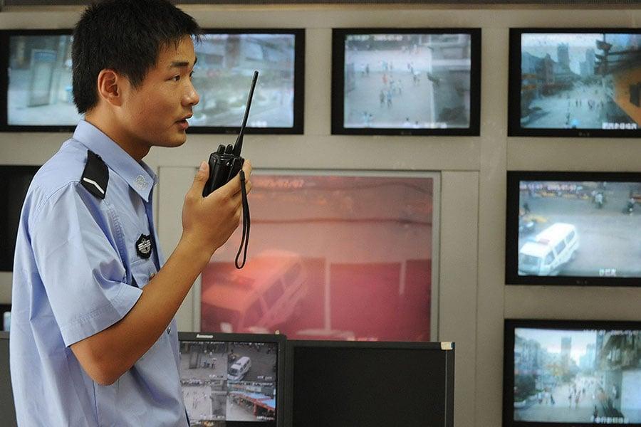 以「維穩」為藉口監控民眾是公安部最大的任務。中國每年出現數以萬計的民眾抗議事件,比較常見的原因是政府腐敗和官方濫用權力。圖為2009年7月12日,安徽省合肥近郊一名警察在使用對講機,其背後是路燈監控攝像機發回的鏡頭。(AFP/AFP/Getty Images)