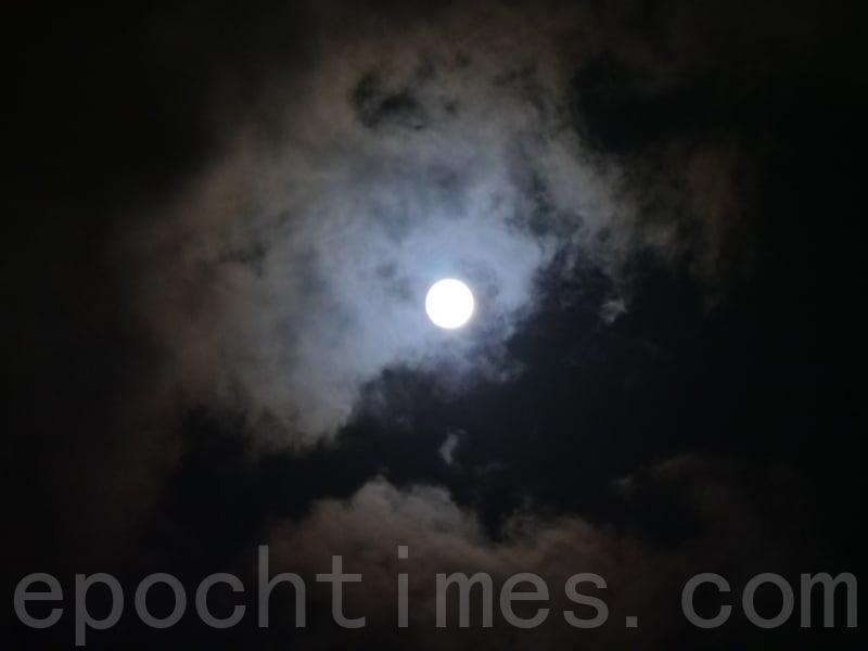 今年中秋節天氣欠佳,月亮被雲層遮蓋,偶爾才露面。(郭威利/大紀元)