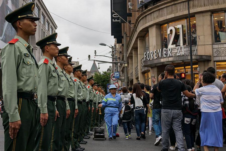 十一期間,上海武警監視過往的民眾。(CHANDAN KHANNA/AFP/Getty Images)